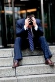 4365993-distraught-businessman-sitting-outside-with-head-in-hands